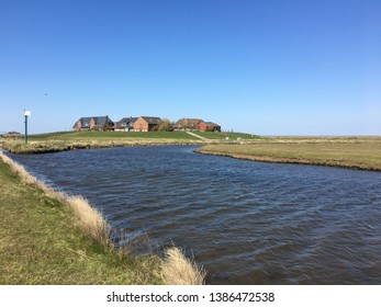 Hallig Hooge, Schleswig-Holstein/Germany - 04/16/2019 Hallig Hooge is situated in the North sea and consists of tidal creeks and marshland. This dwelling mound with the school is called Ockelützwarft.