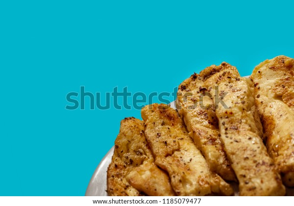 Halloumi strips on a plate with cyan background