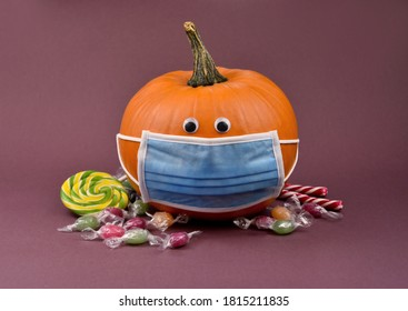 Hallowee pumpkin with protective mask and candies stock images. Funny halloween pumpkin with coronavirus mask and pile of sweets photo. Pumpkin wearing medical mask on face to prevent flu images