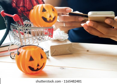 Halloween accessories and costume on shopping cart with woman using mobile phone and credit card, Happy Halloween