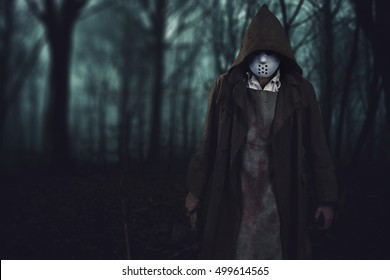halloween background - bloody serial killer with ax in the dark scary woods