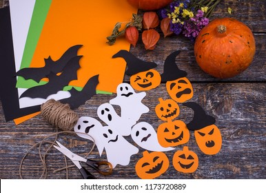 Halloween background with colored paper, handcraft scary pumpkins, black hats, bats, flying scary specters, pumpkin vegetable, flowers on a wooden table.