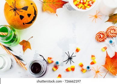 Halloween background with drinks, candies and decor on white table. Copy space. Top view