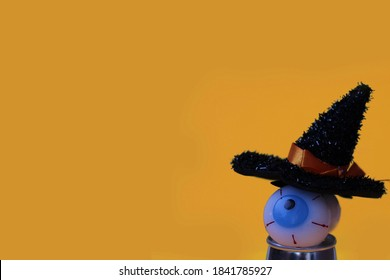 Halloween background, eyeball  with a black witch hat on an orange background, close up, isolated, halloween template