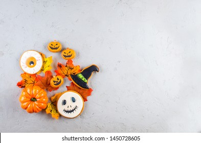 Halloween background with gingerbread cookies, pumpkin, candies and autumn leaves on on gray concrete background, copy space, top view, flat lay, mockup