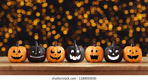 Halloween background with glitter pumpkin characters decor on wooden table and bokeh lights