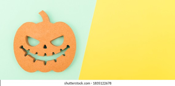 Halloween background idea.Flat lay wooden Jack o lantern spooky pumpkin on green yellow paper color background.Halloween design with copy space for text advertising.Background idea in Autumn October.