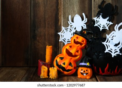 Halloween background Jack-o pumpkin head lantern decoration with old candle and magical pot on spider web wood texture background