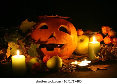 Halloween background, pumpkin mask with candles and lantern flowers and apples.