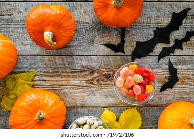 Halloween background. Pumpkins, paper bats and autumn leaves on wooden background top view copyspace