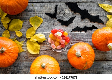 Halloween background. Pumpkins, paper bats and autumn leaves on wooden background top view