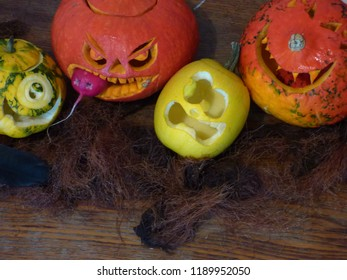 Halloween background, rustic style, blank space for text. Funny scene on a dirty table, spooky pumpkins, screaming yellow squash, cyclops pattypan,black plume crow.