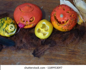 Halloween background, rustic style, blank space for text. Funny scene on a dirty table, spooky pumpkins, screaming yellow squash, cyclops pattypan,black plume crow, corn.