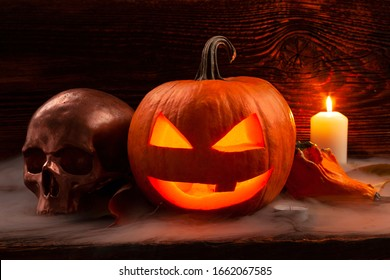 Halloween background. Scary pumpkin and spooky skull on wooden baclground.