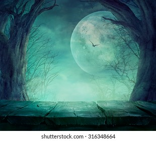 Halloween background. Spooky forest with full moon and wooden table