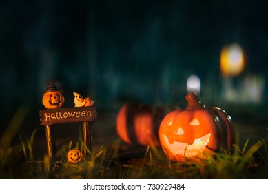 Halloween background with a Spooky pumpkin and halloween decorated in dark forest.