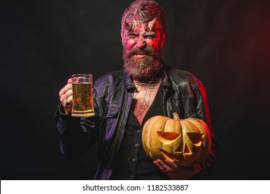 Halloween bad habits and addiction concept. Hipster demon drink beer on black background. Holiday celebration and party. Devil smile with glass mug. Man with satan horns hold pumpkin.