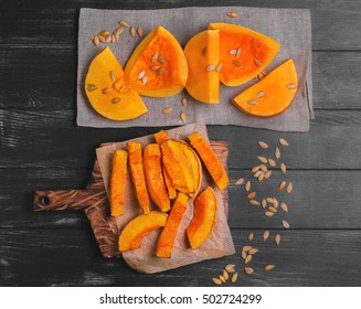 Halloween Baked pumpkin pieces on wooden board, raw pumpkin pieces cut for baked, napkin tissue, pumpkin seeds on dark black background, top view