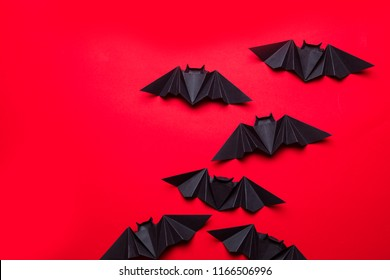 Halloween bats made from paper on a red background