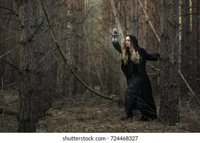 Halloween. beautiful girl with a lantern in a black dress in the forest