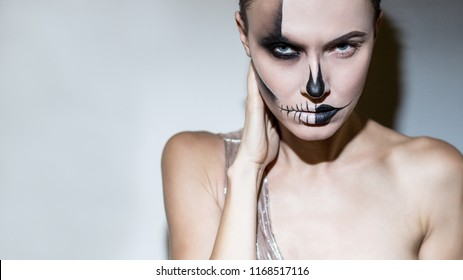 Halloween. Beautiful woman with bright black halloween makeup isolated over gray background