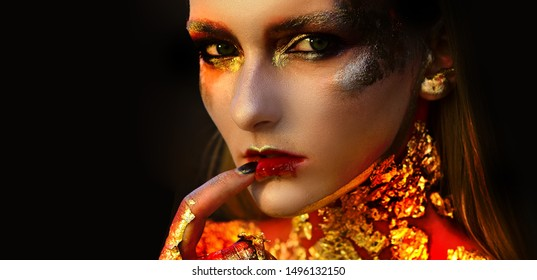 Halloween beauty Witch girl portrait with golden make-up. Halloween Witch with red bloody lips and golden skin. Halloween design make up