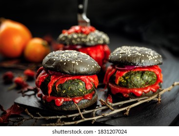 Burgers noirs d'Halloween avec des boulettes de légumes, poivrons rouges grillés et ketchup. Idée de cuisine pour Halloween
