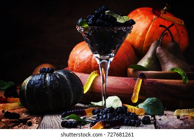 Halloween black candy in a glass and pumpkin guards, vintage wooden background, low key, selective focus