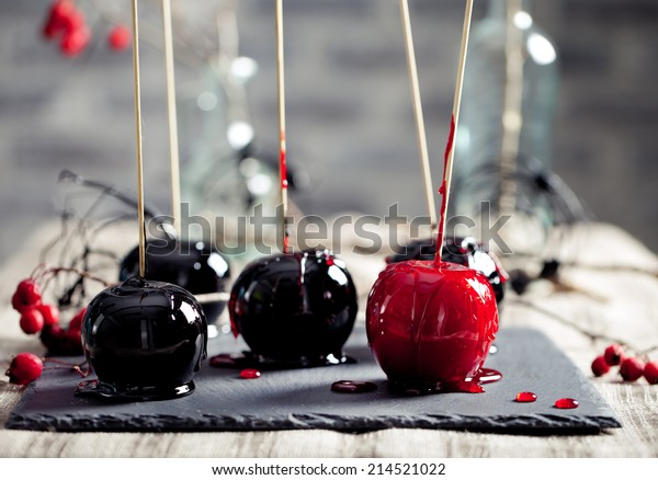 Halloween black and red caramelized apples on a wooden sticks. Traditional dessert. Selective focus.