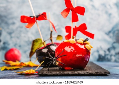 halloween black and red poisoned caramelized apples with peanuts on wooden sticks with bows. Sweet candy apple dessert for halloween party. Greeting card. Copy space
