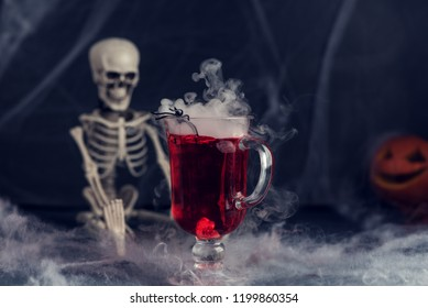 Halloween bloody cocktail with skeleton