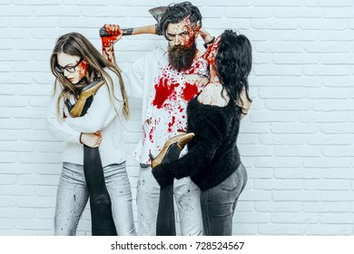 Halloween bloody man standing with girls. People on white brick wall. Bearded hipster with axe and red blood. Women holding female legs. Halloween holiday celebration concept