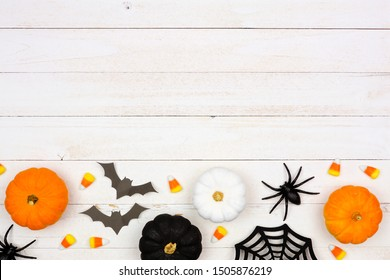 Halloween bottom border with black, orange and white decor and candy over a white wood background. Top view with copy space.