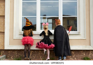 Halloween boy and girls looking through window of house from outside