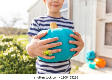 Halloween boy with teal pumpkin in hands.  trick or treating.  Teal Pumpkin Project. Alternative non-food treats for kids with food allergies. the concept of health for children in the Halloween season