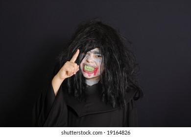 Halloween boy with warning gesture over dark background