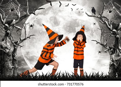 Halloween.Two brothers in costume walking in a scary woods. Scare each other with scary spiders