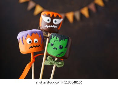 Halloween cake pops and chocolate dipped marshmallow with funny monster faces. Selective focus.