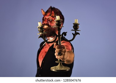 Halloween candlestick with wax candles in hand of blurred man devil with horns, red blood, wounds on blue background. Flesh, soul, divinity concept.