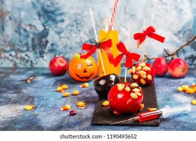 Halloween candy bar for kids with creepy party drinks in syringe, caramelized apples and selection of candies