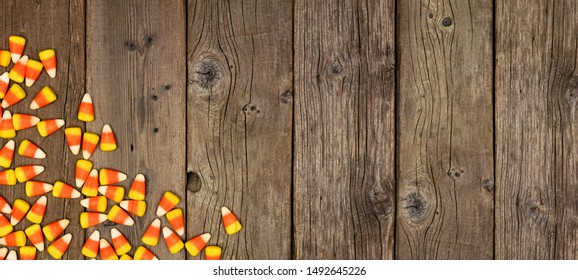 Halloween candy corn corner border banner. Top view on a rustic wood background with copy space.