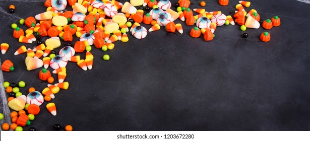 Halloween candy scattered over a black chalkboard background, room for copy space.