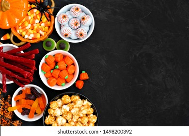 Halloween candy side border over a black stone background with copy space. Assortment of sweet, spooky treats. Top view. Buffet party food concept.