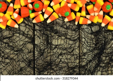 Halloween candy top border against a rustic wood and spooky black cloth background