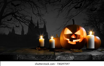 Halloween card with pumpkin and candles, gothic castle, trees and flying bats silhouette on background