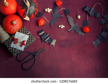 Halloween card with pumpkins , garland of paper cut bats, red background, flat lay,top view