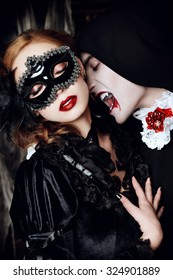 Halloween carnival. Bloodthirsty male vampire in medieval dress is biting a beautiful lady in mask. Halloween.