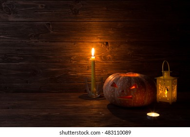 Halloween carved pumpkin and candle on wooden background. Halloween pumpkin background. Jack-O-lantern.