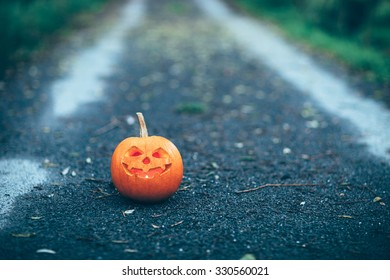 Halloween carved pumpkin or jack-o'-lantern in a path with a candle inside. Shallow depth of field image.