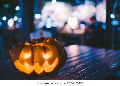 Halloween Carved Pumpkin on a City Street. Jack-o'-Lantern decoration illuminating with burning candle inside.